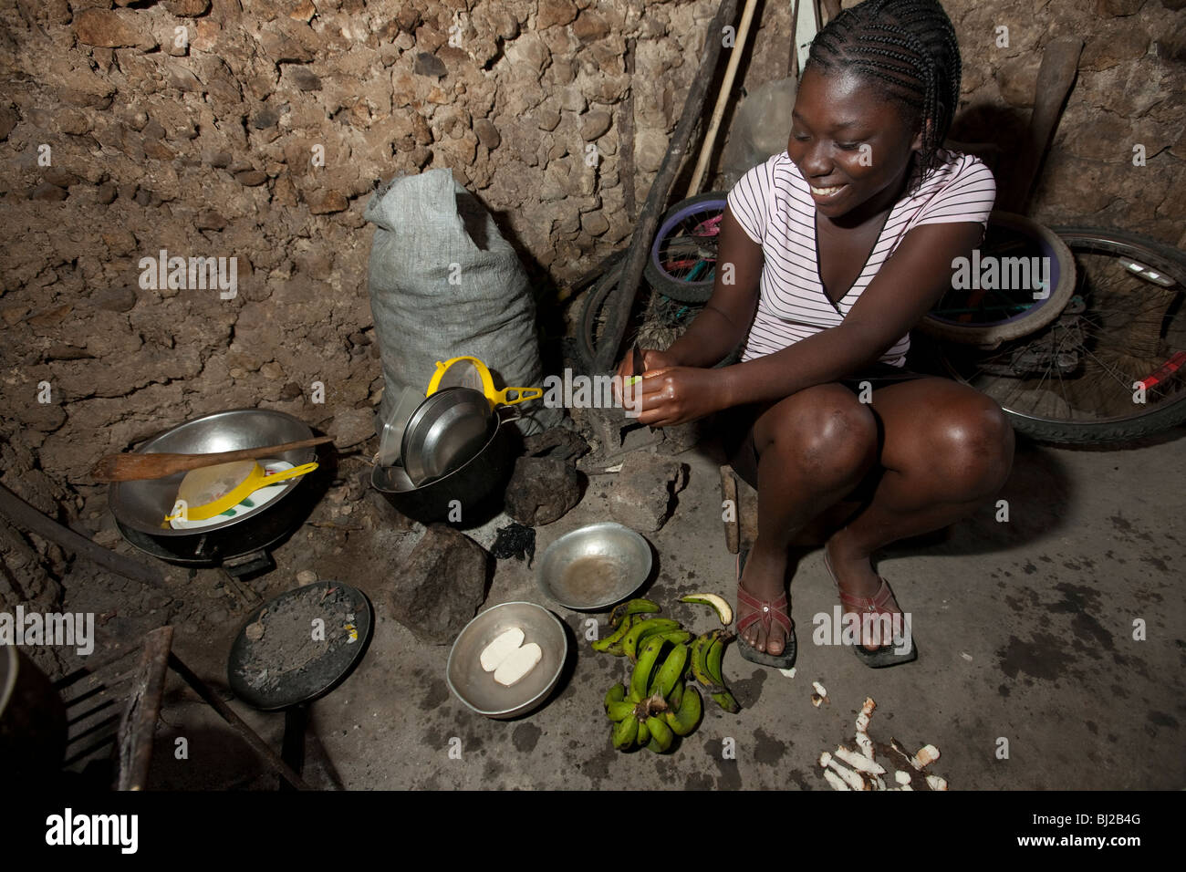 A young woman cooks in her kitchen in Mirebalais. - Stock Image