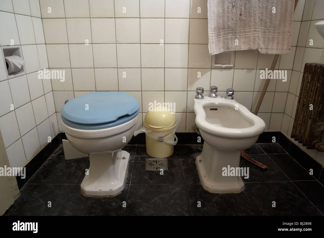 toilet with closed lid and bidet in a run down bathroom - Stock Image
