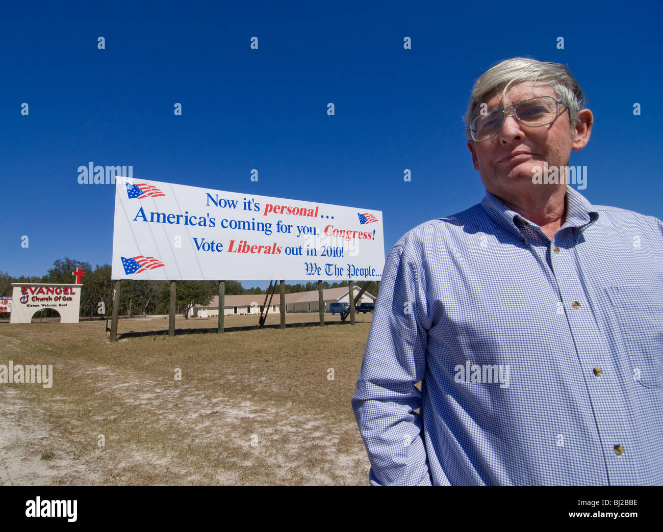 Florida resident John Knapp stands beside his conservative billboard warning the liberal US Congress about upcoming - Stock Image