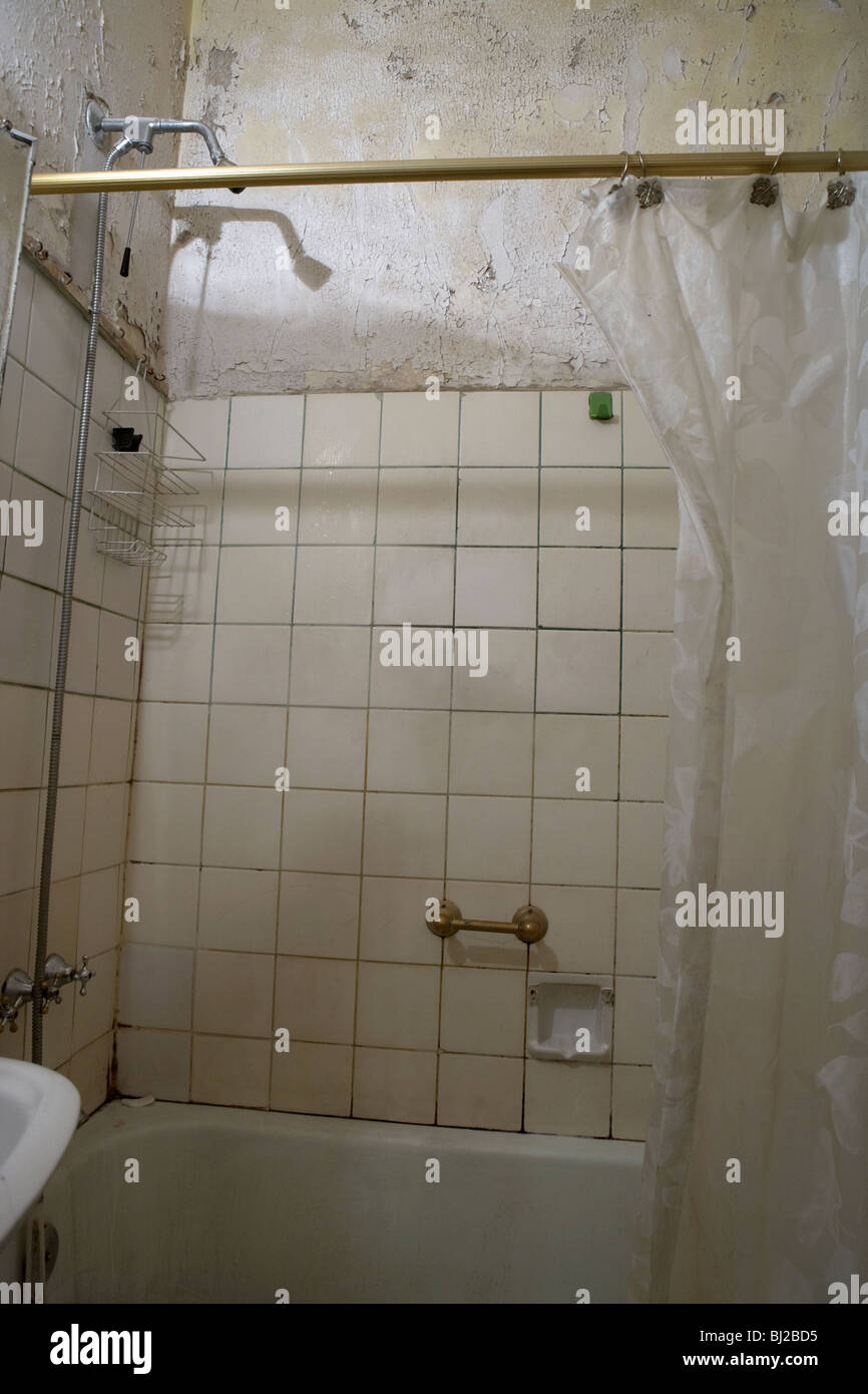 decaying shower in a run down bathroom - Stock Image