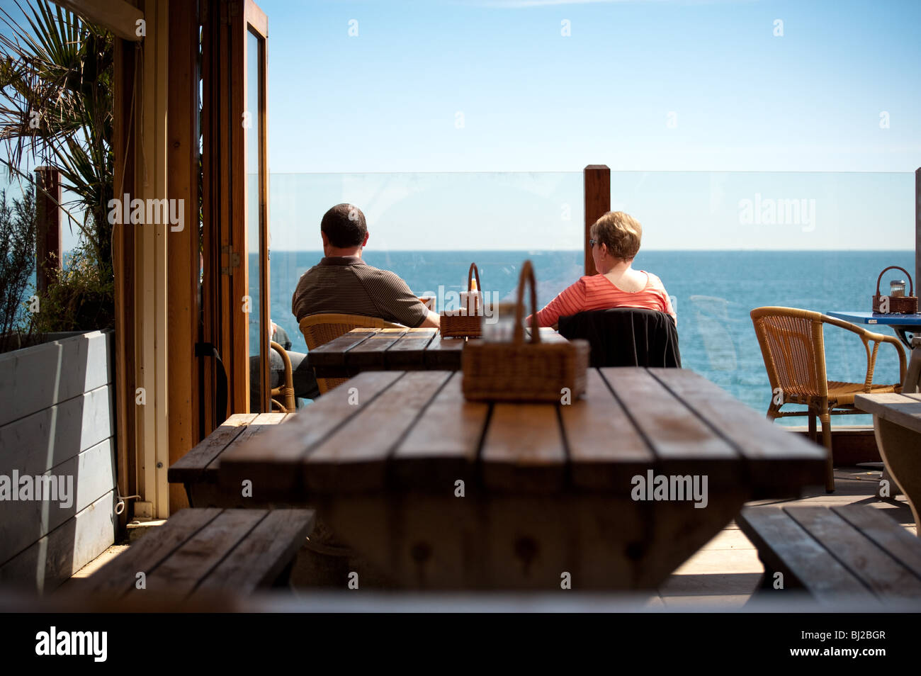 Couple enjoying an afternoon drink in the sun at a beach cafe at Blackpool Sands, Devon - Stock Image