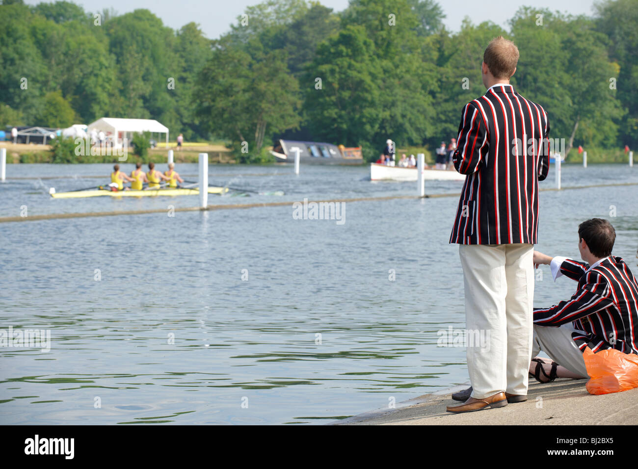 Spectator watching a race at the Royal Henley Regatta from the river side - Stock Image
