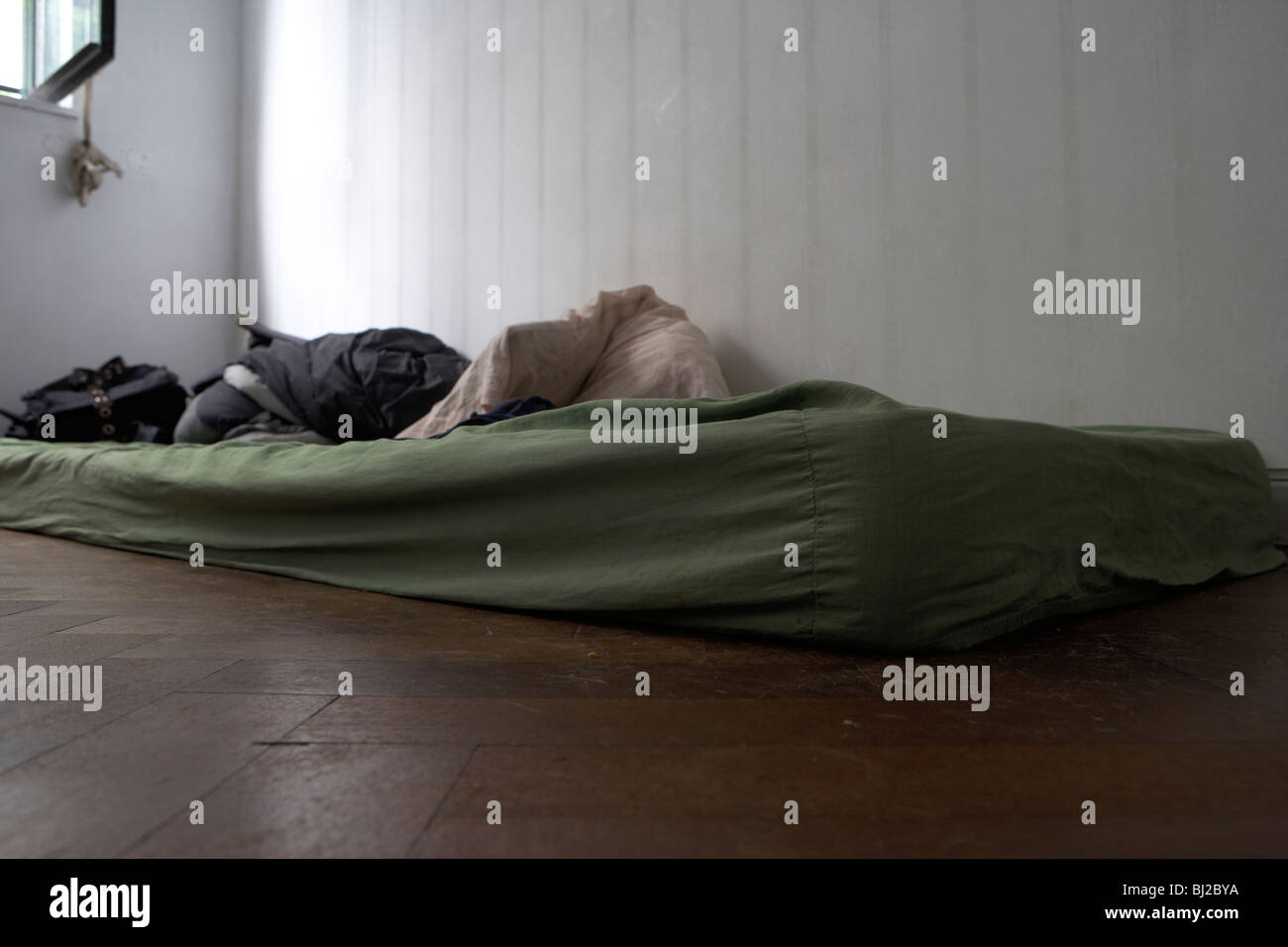 old dirty mattress lying on the floor in a bedroom - Stock Image