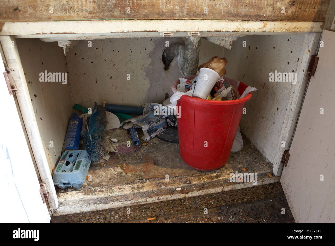 dirty unhygienic under sink in a dirty run down kitchen in south america - Stock Image