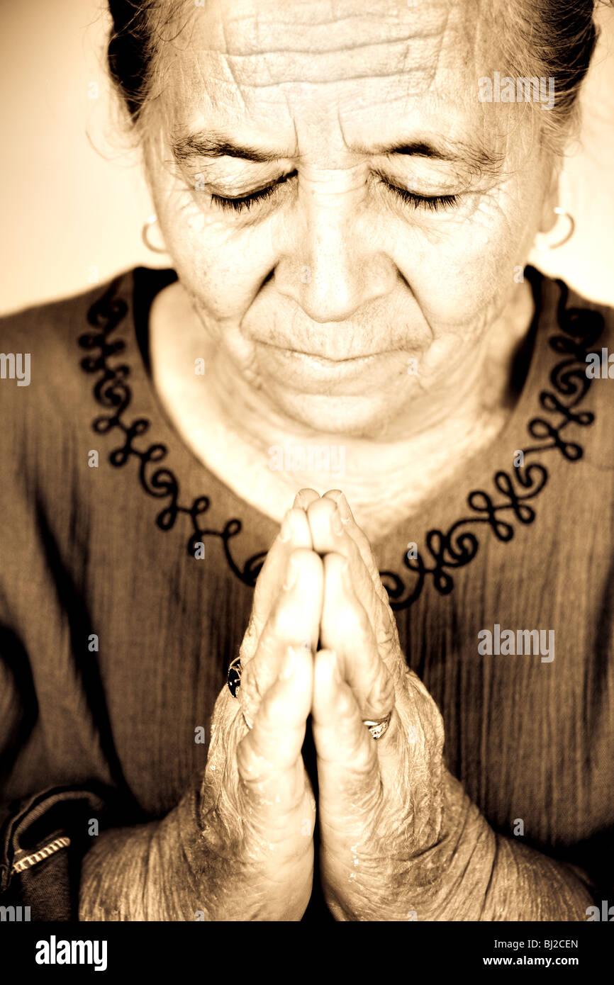 Christian religious senior woman praying to God - Stock Image