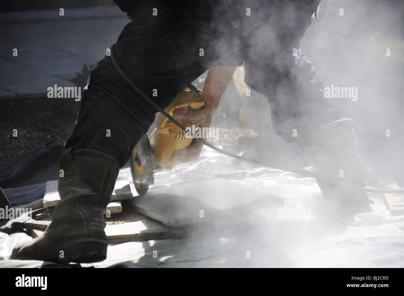 Workman cutting paving slabs for terrace with angle grinder - Stock Image