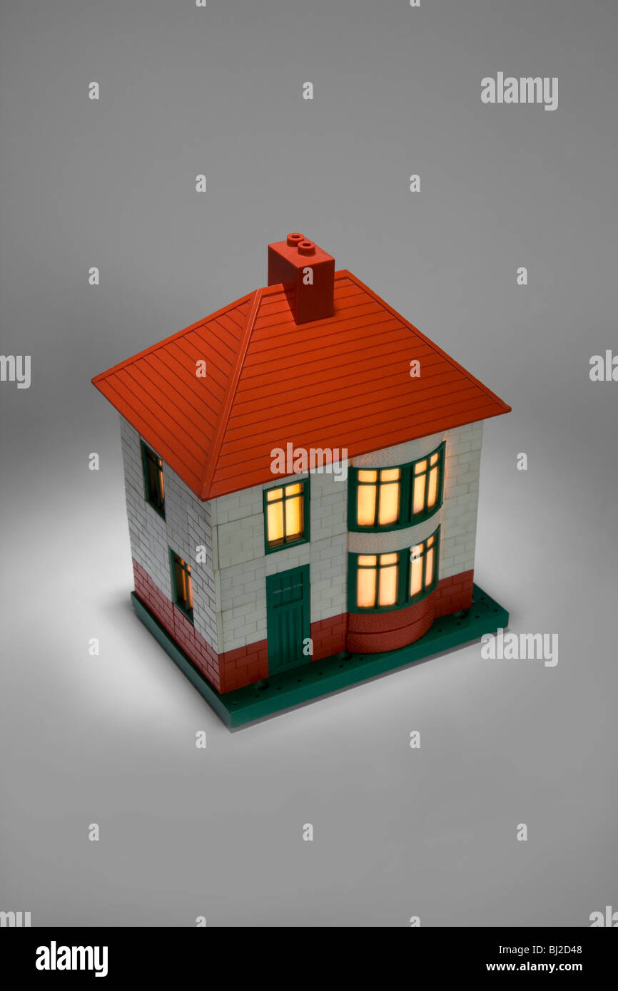 A model 1950's Bayko toy house on grey background with simulated house lights - Stock Image