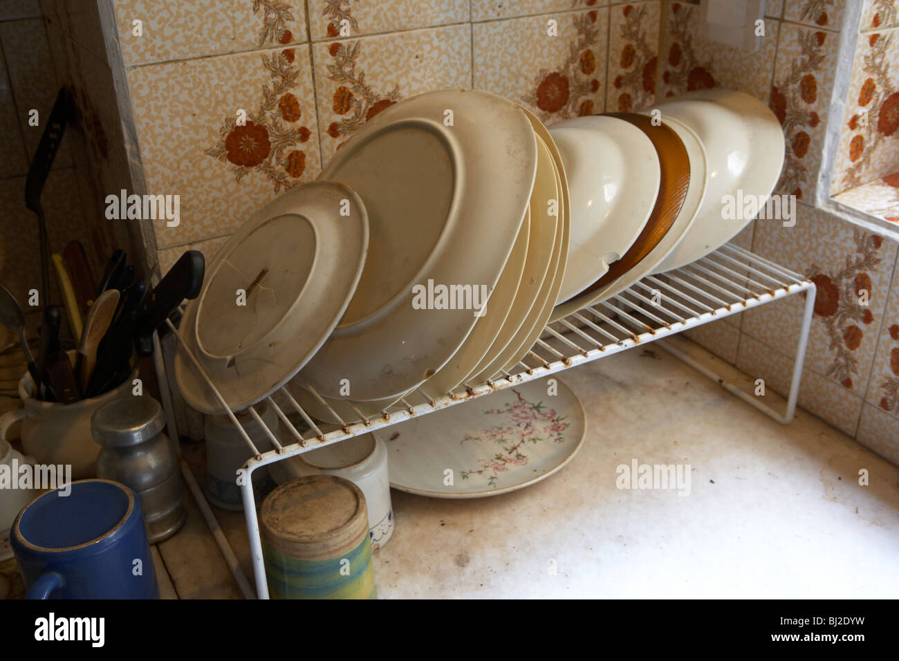 row of chipped cracked plates in a dirty run down kitchen in south america - Stock Image