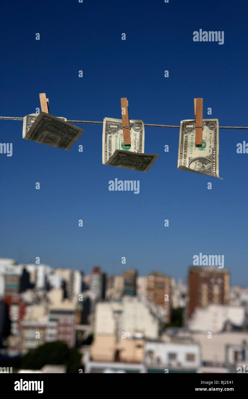 three one dollar bills blowing in the wind hanging on a washing line with blue sky over a city skyline - Stock Image