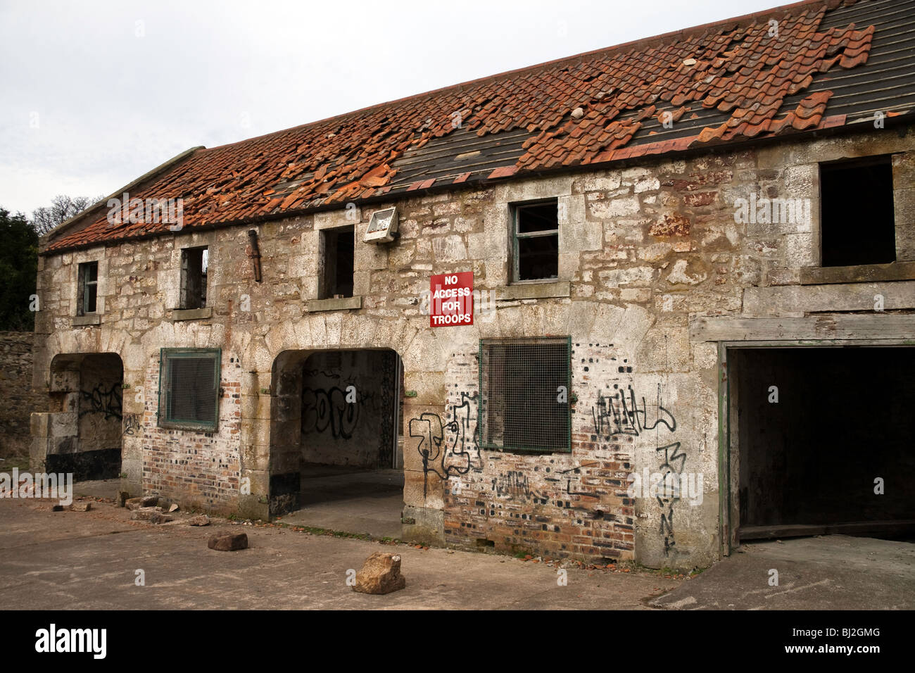 A deserted, run-down building in a state of disrepair. A sign on the wall reads 'No Access for Troops' - Stock Image
