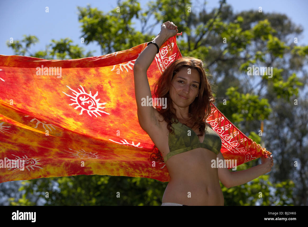 young hispanic latin woman putting a wrap over herself to shade from sunlight in the park in buenos aires argentina - Stock Image