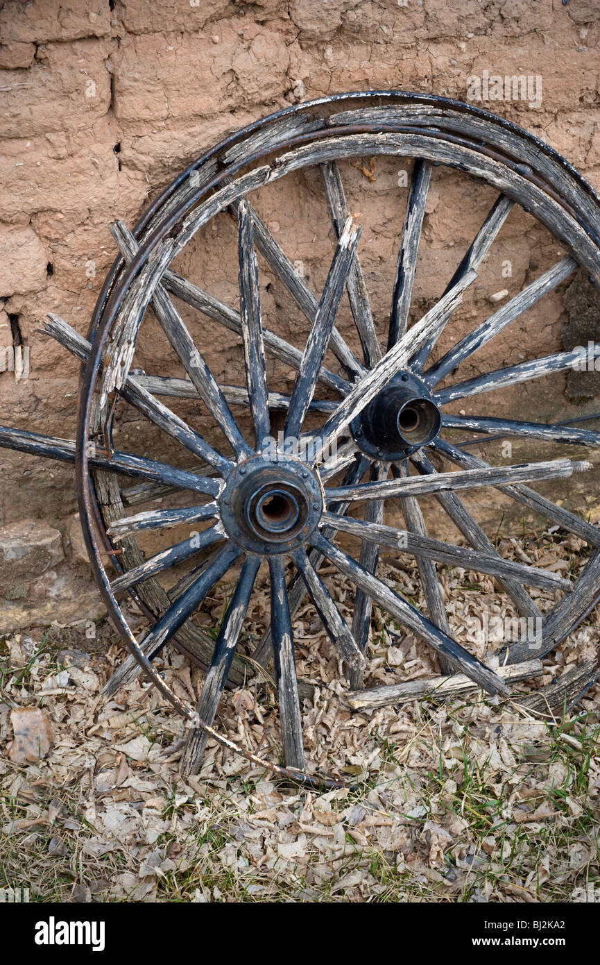 Old wagon wheels lean against an adobe brick wall in the historic town of Lincoln, New Mexico. - Stock Image