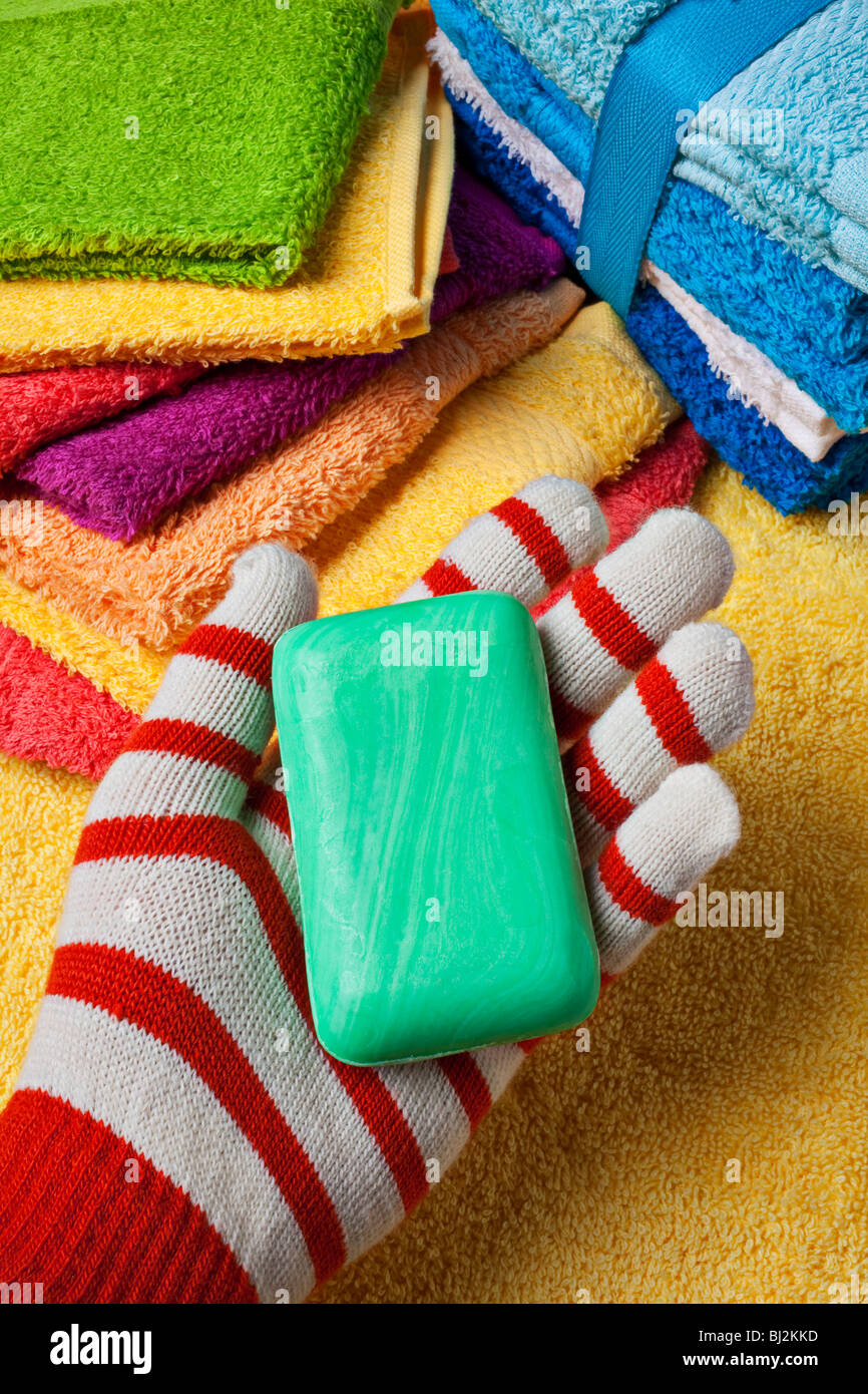 Gloved hand holding green bar of soap - Stock Image