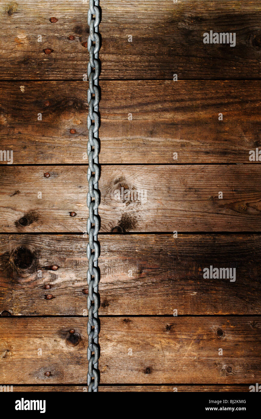 A chain hanging down a rustic wooden wall. - Stock Image
