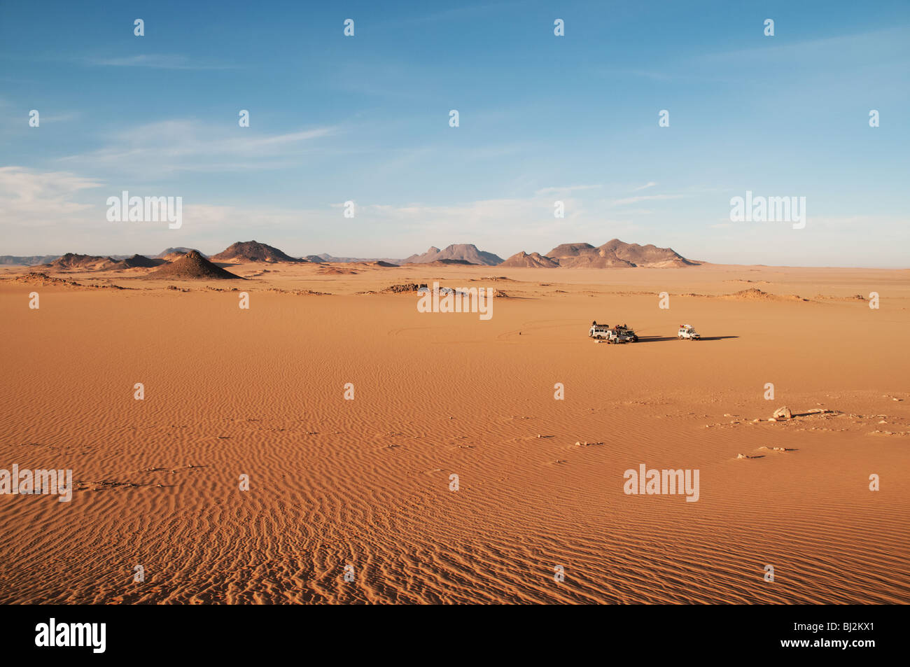 A jeep convoy making camp among the red sands of the Uweinat region of the Sahara Desert, Western Desert, Egypt - Stock Image