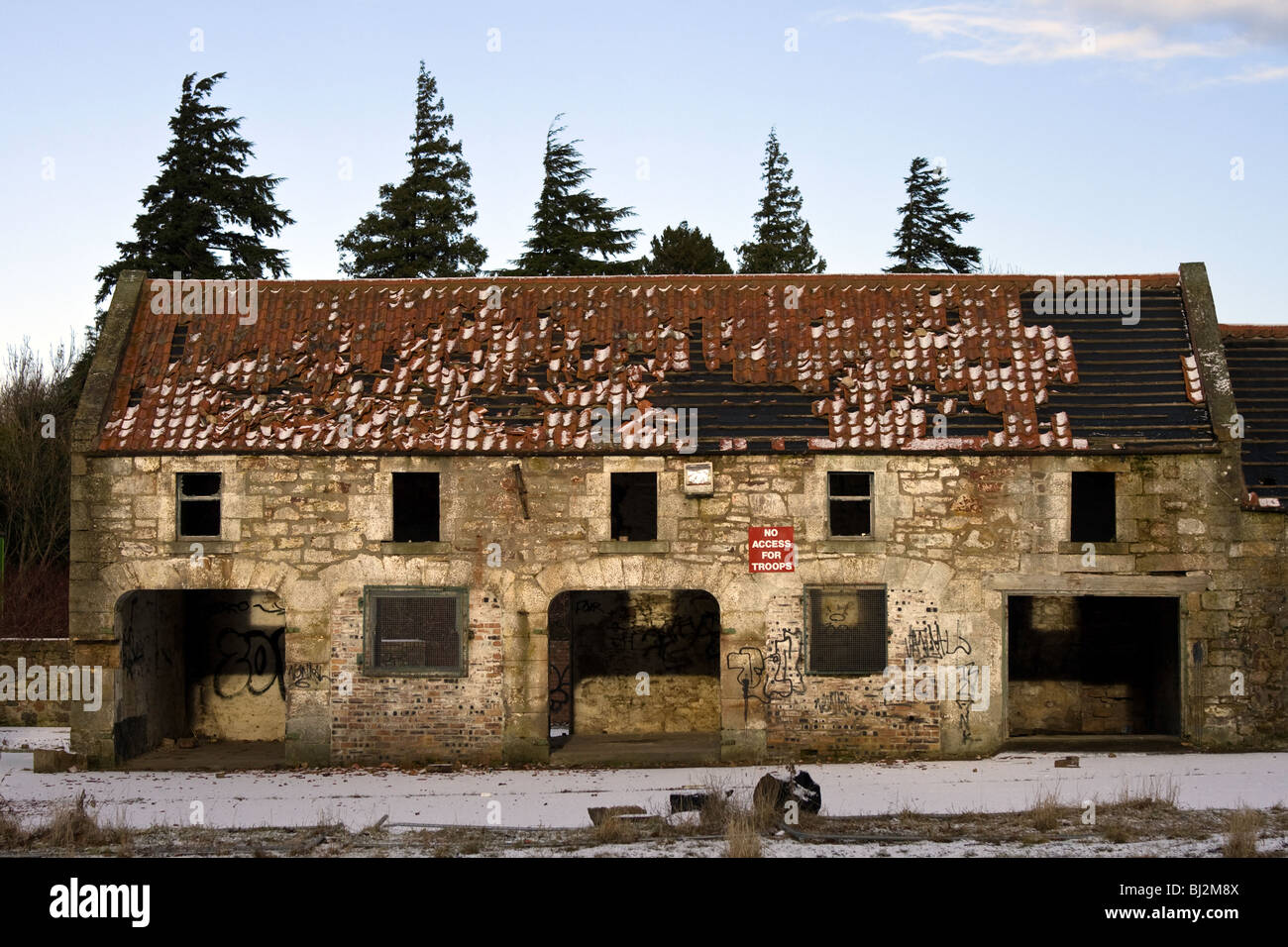 An abandoned building on a winter's day. A sign on the wall reads 'no access for troops' - Stock Image