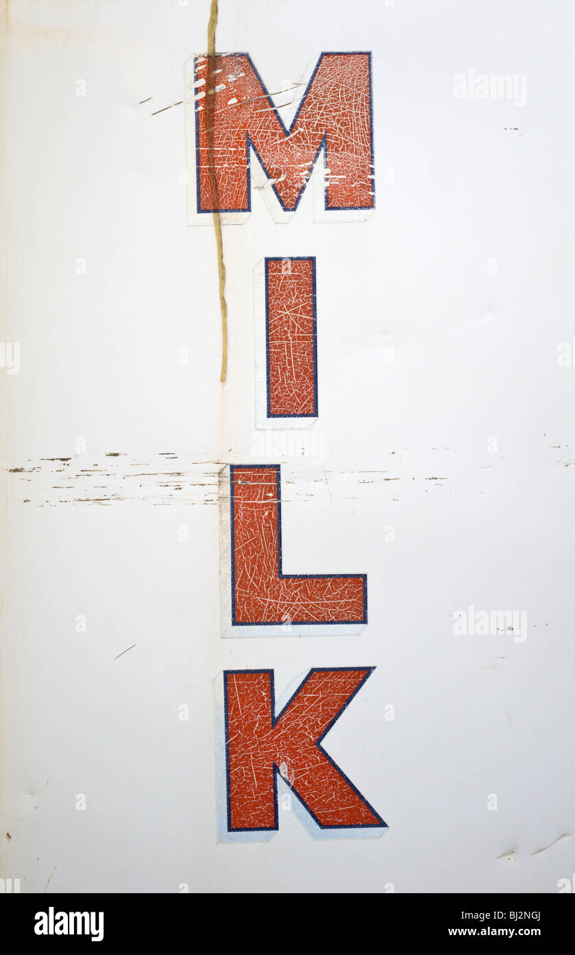An old dented and scratched milk sign in Billy the Kid's wild west town of Lincoln, New Mexico. - Stock Image