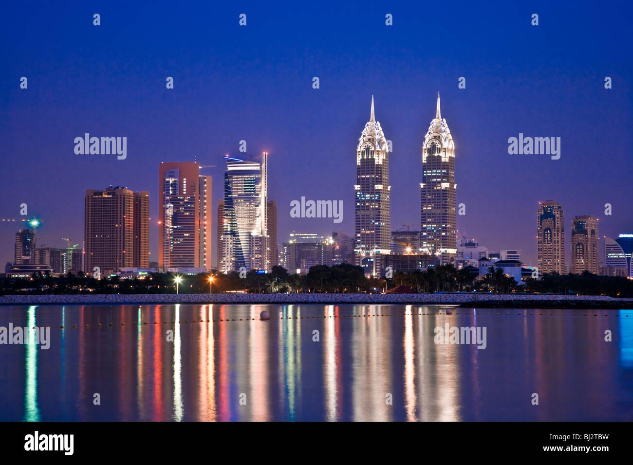 Twilight view over Dubai from Palm Island Jumeirah with the twin copies of the Chrysler Building in New York in - Stock Image