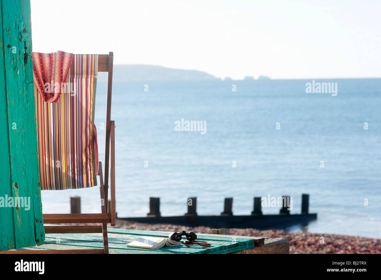 Empty deck chair by beach - Stock Image