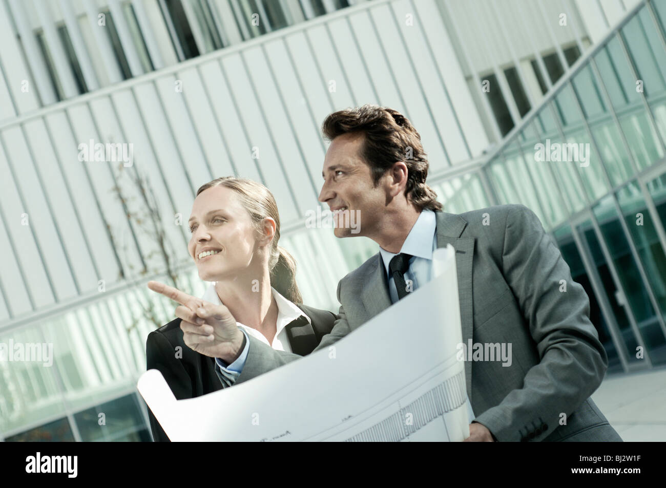 Businesspeople going over blueprints - Stock Image