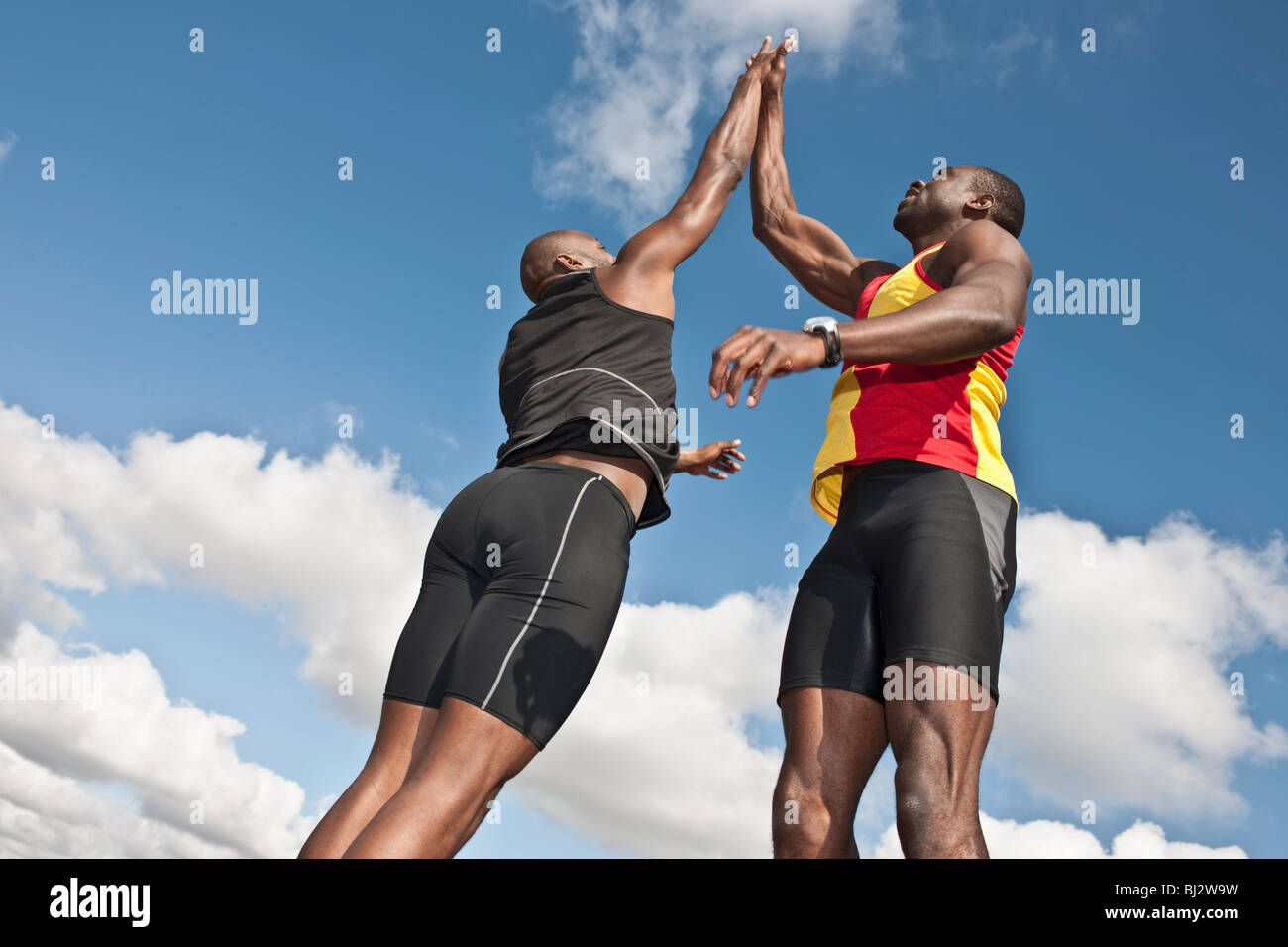 2 male athletes jumping with high 50s - Stock Image