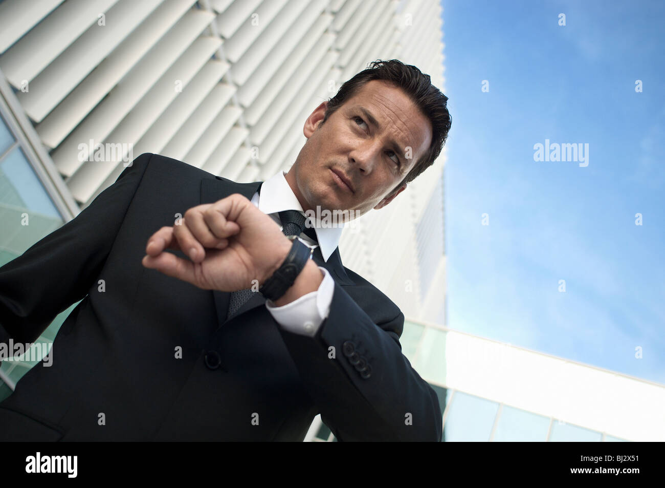 Businessman keeping time with watch - Stock Image