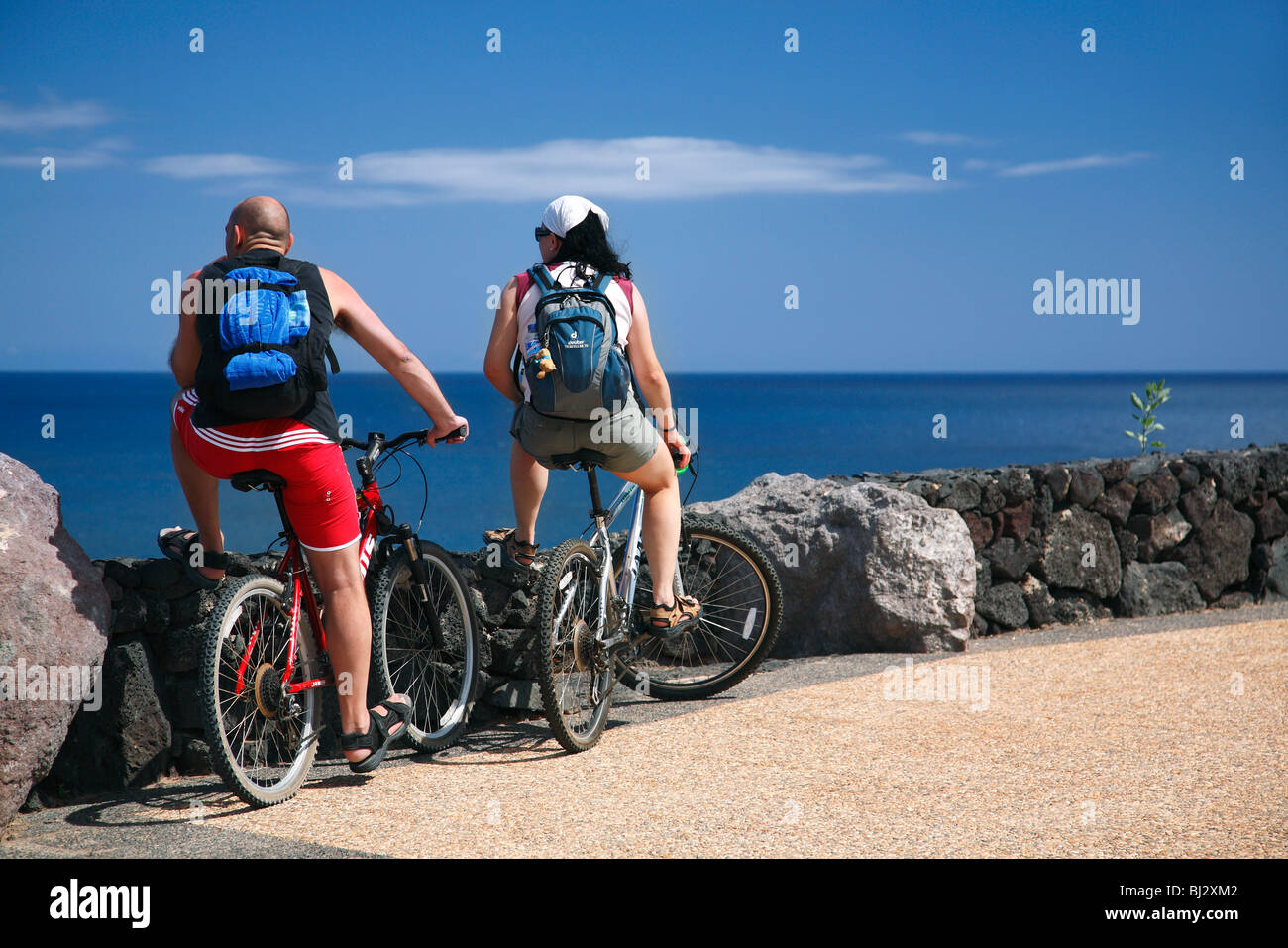Tourists riding bicycles looking over the sea, Lanzarote, Canary Islands, Spain - Stock Image