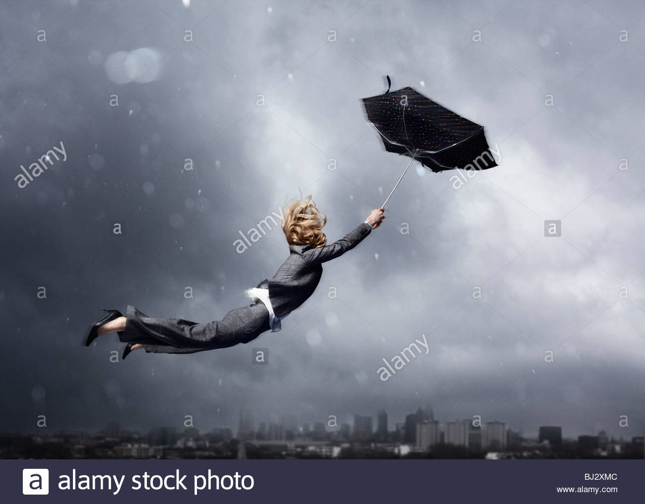 Woman being blown away by an umbrella - Stock Image