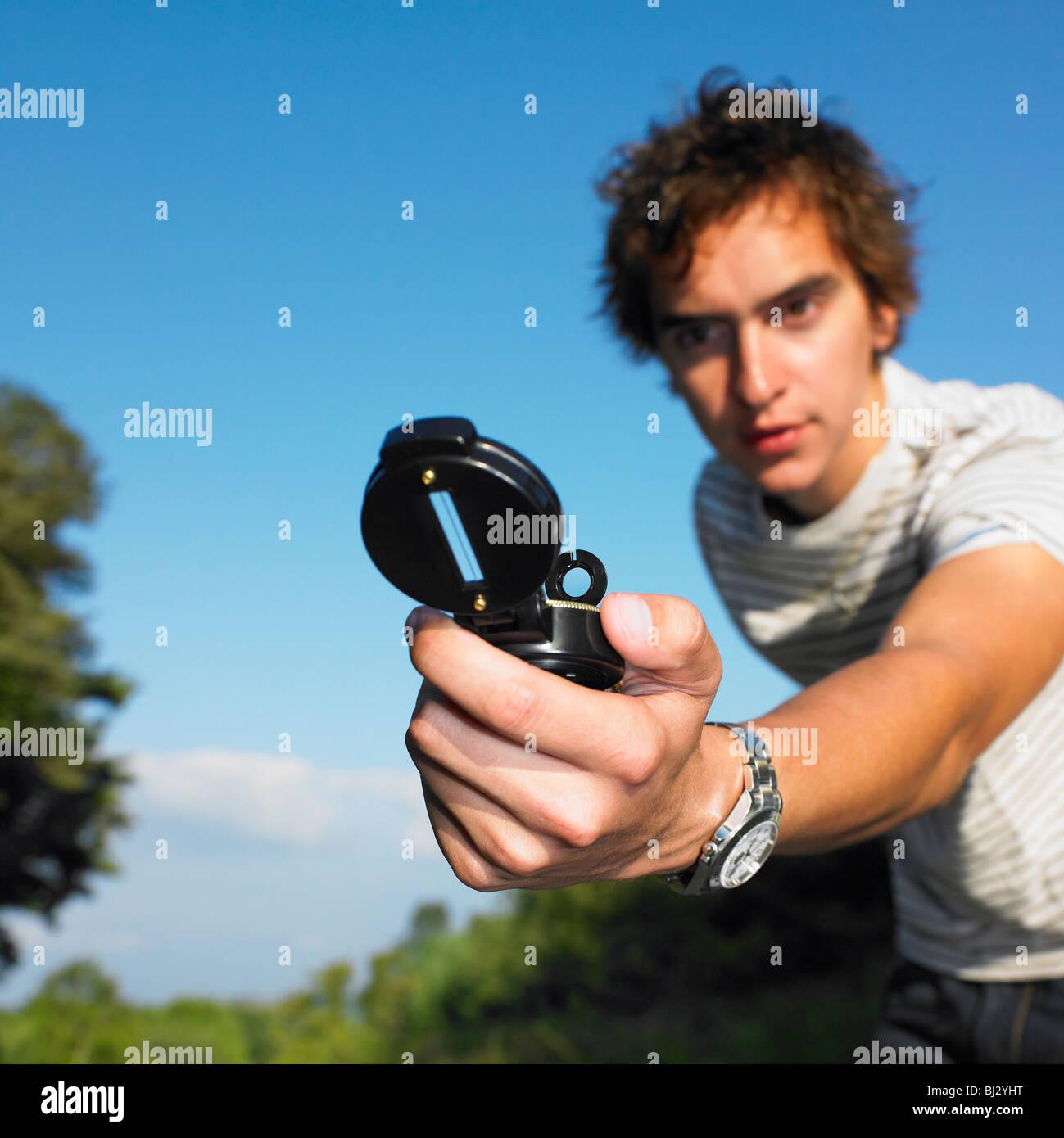 Man looking at compass - Stock Image
