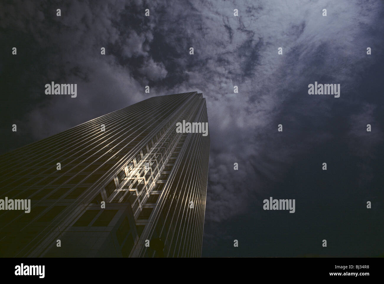 Canary Wharf tower rises to the clouds above in London Docklands, England. - Stock Image