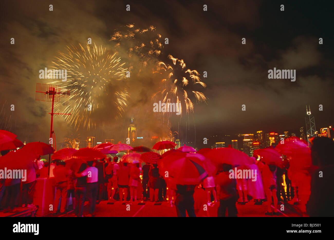 Crowds gather beneath umbrellas at the stroke of midnight to witness the transfer of sovereignty of Hong Kong from - Stock Image