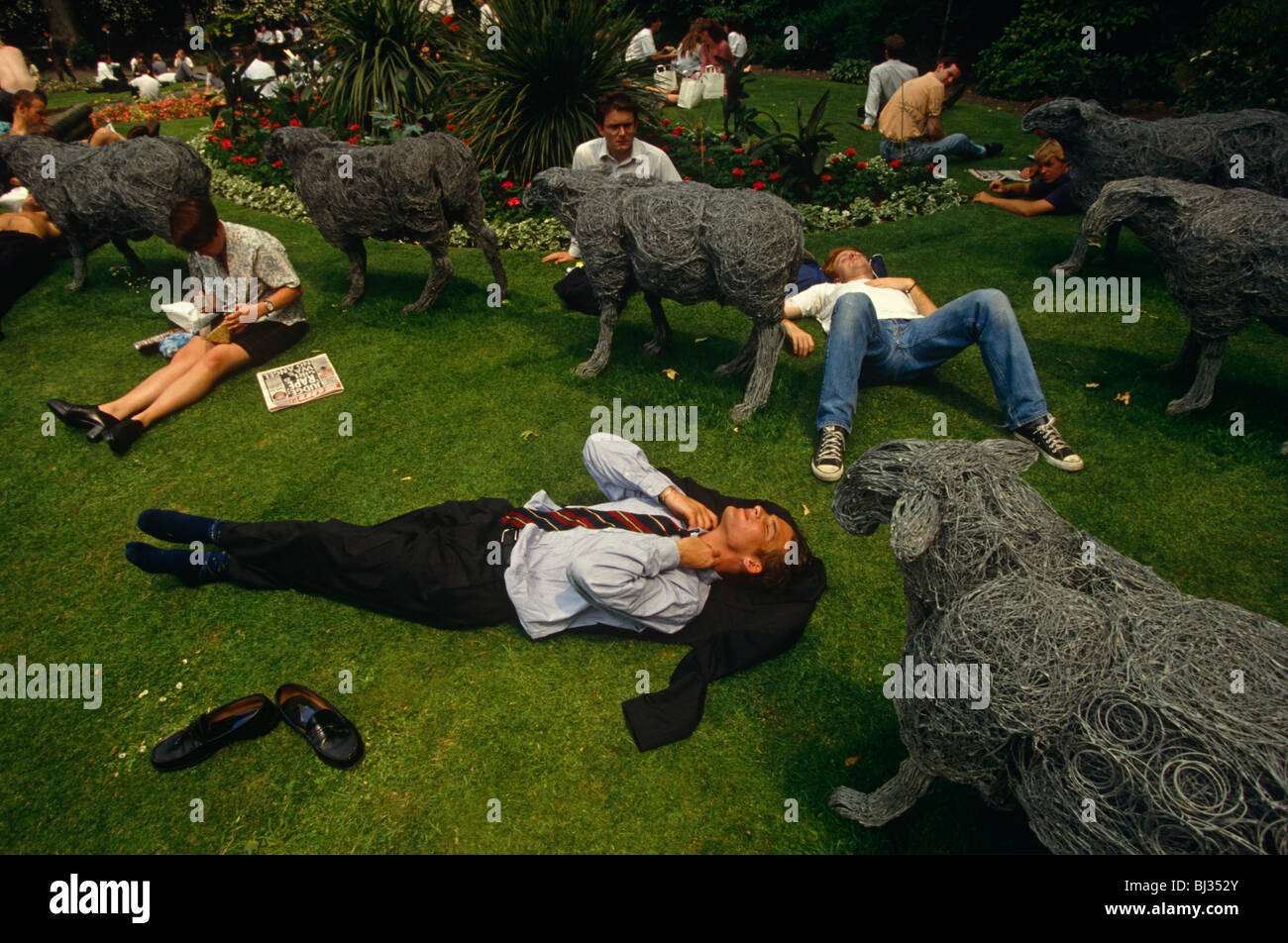 Office and business workers lie down in the grass in their lunch break at Finsbury Circus surrounded by steel sheep - Stock Image