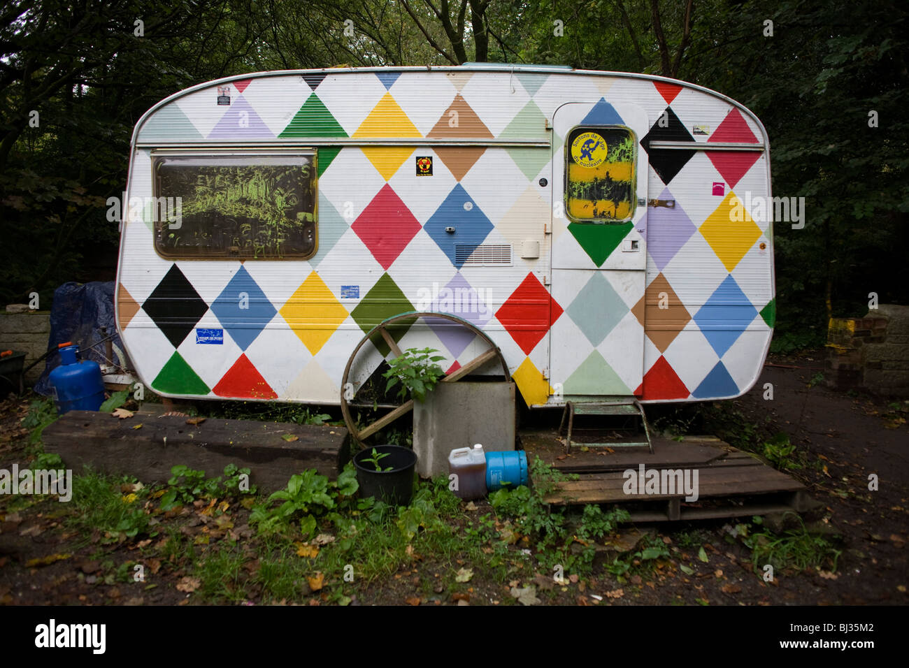 A customized harlequin-patterned caravan sits in the damp woods at the Faslane Peace Camp - Stock Image