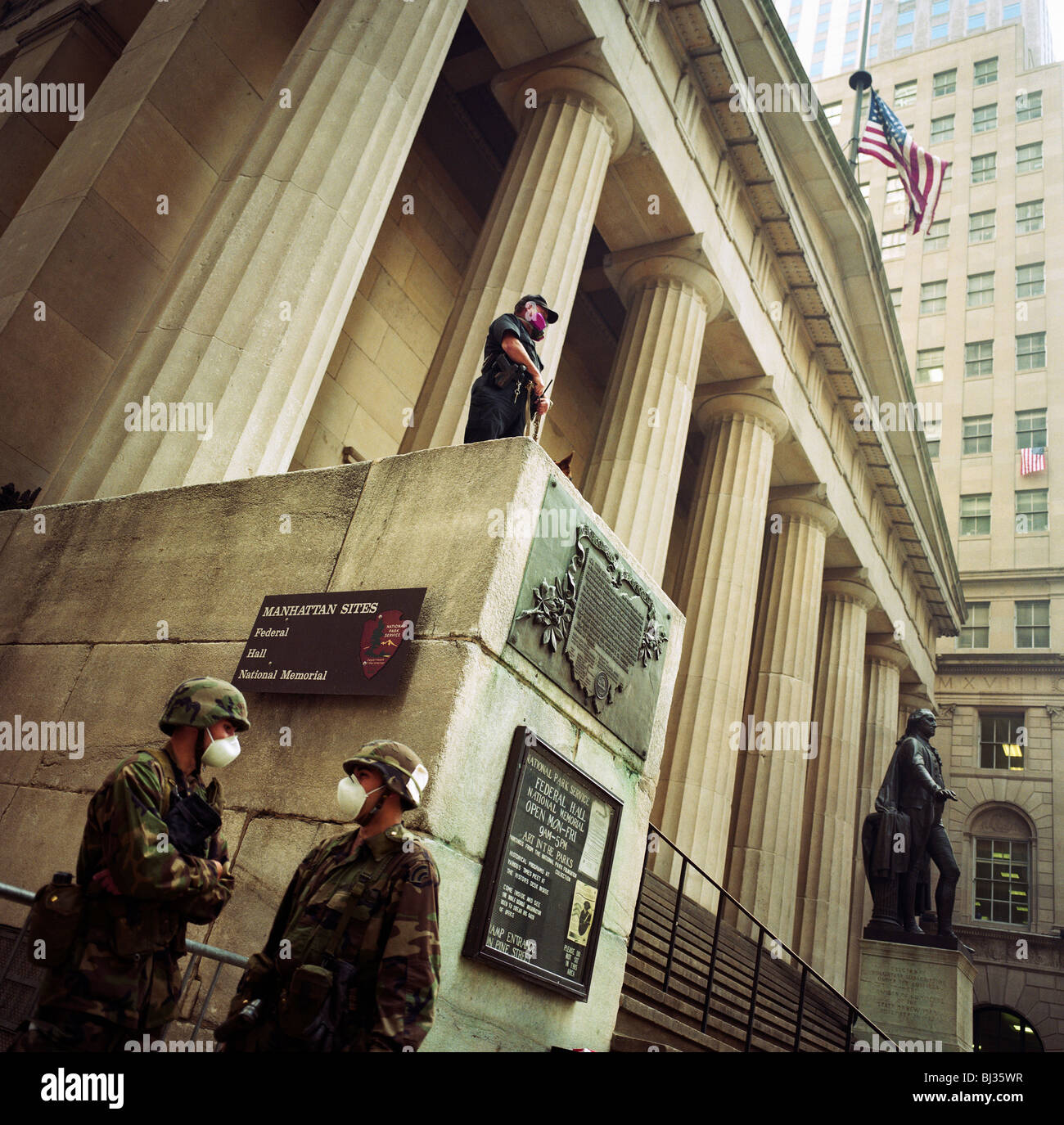 Soldiers of the National Guard wear dust masks and guard the high columns of the Federal Hall on Wall Street. - Stock Image