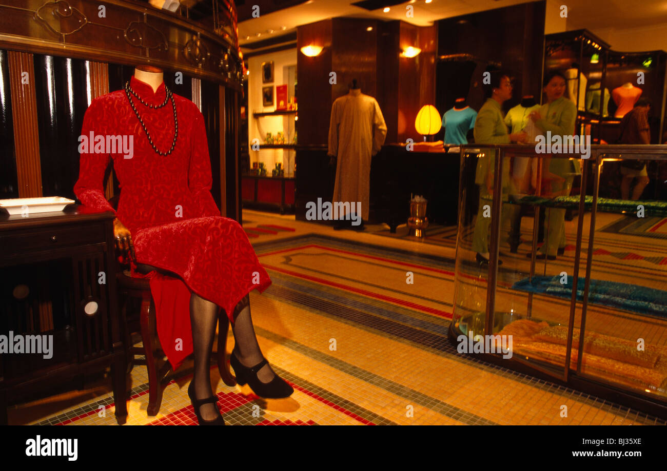 An elegant but headless life-size clothing mannequin seated on a chair on the shop floor of Chinese clothing brand - Stock Image