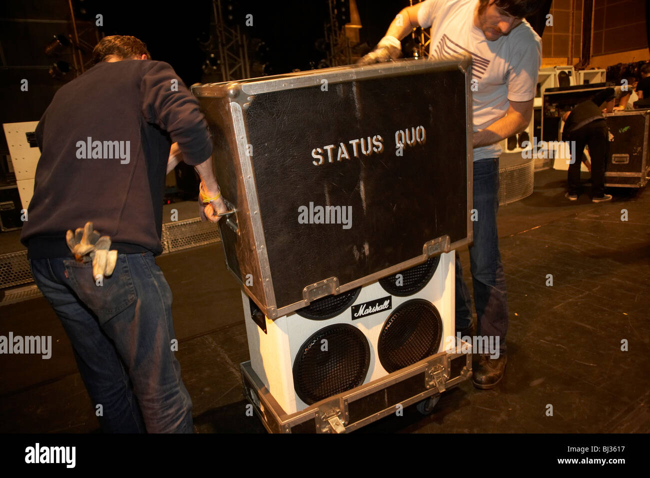 Local French stage hands assist Status Quo roadies to dismantle the stage and pack every item of equipment into - Stock Image