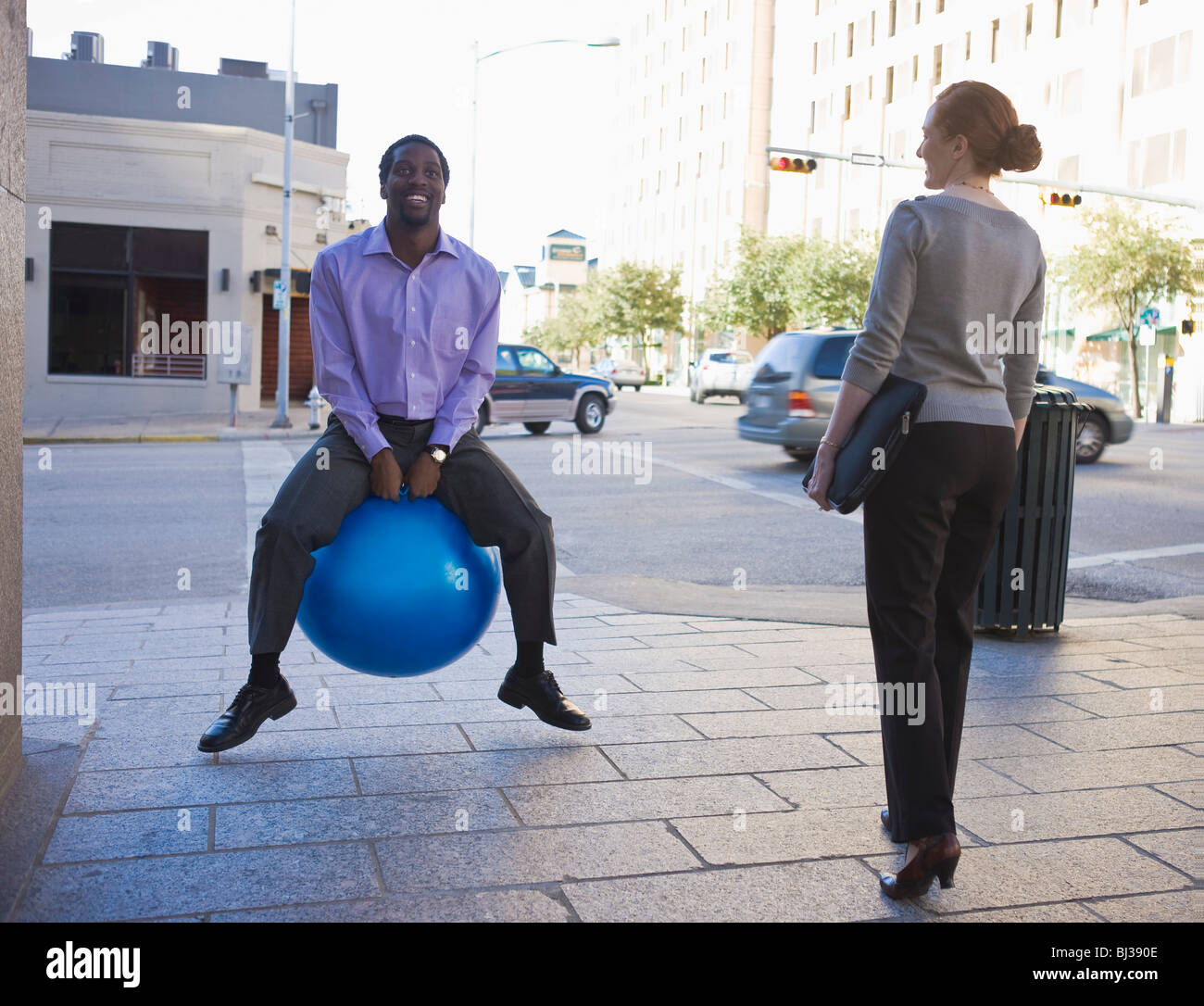 businessman on blue ball in street - Stock Image