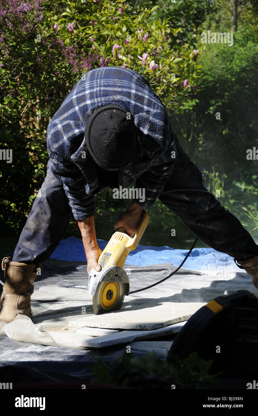 Workman cutting stone paving slabs with angle grinder - Stock Image