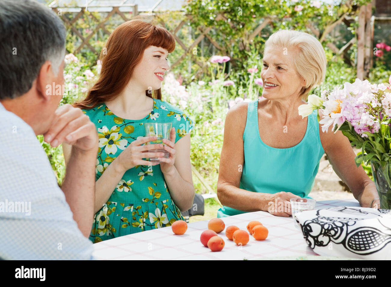 woman talks with mature couple in garden - Stock Image