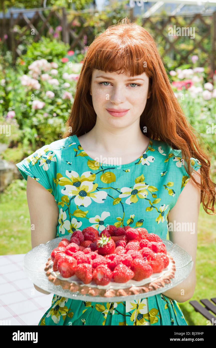 young woman holding strawberry tart. Stock Photo