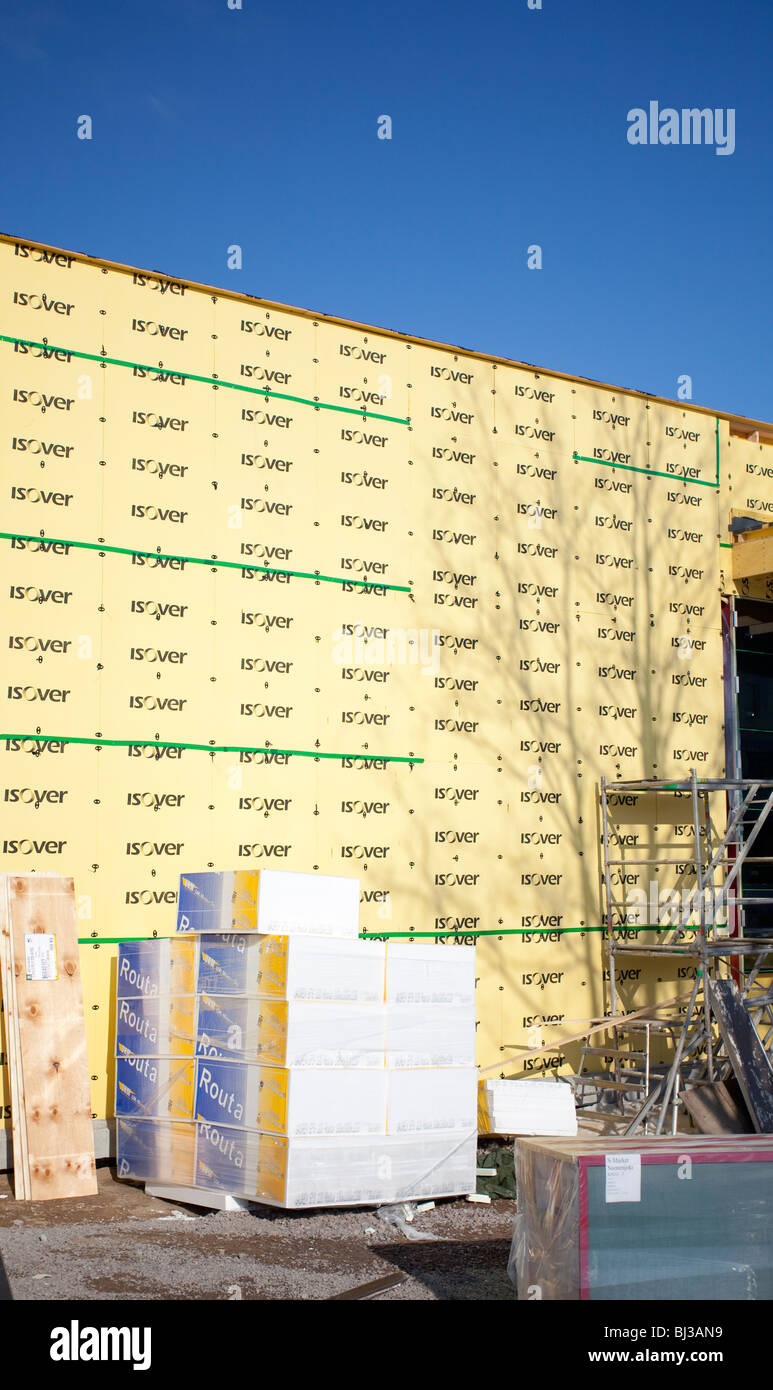 Pile of polystyrene ground frost insulation slabs and the wall lined with Isover mineral wool insulation panels Stock Photo