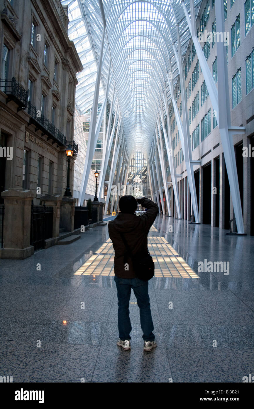 A photographer taking picture of the famous arch support structure inside brookfield place (previously bce place) - Stock Image