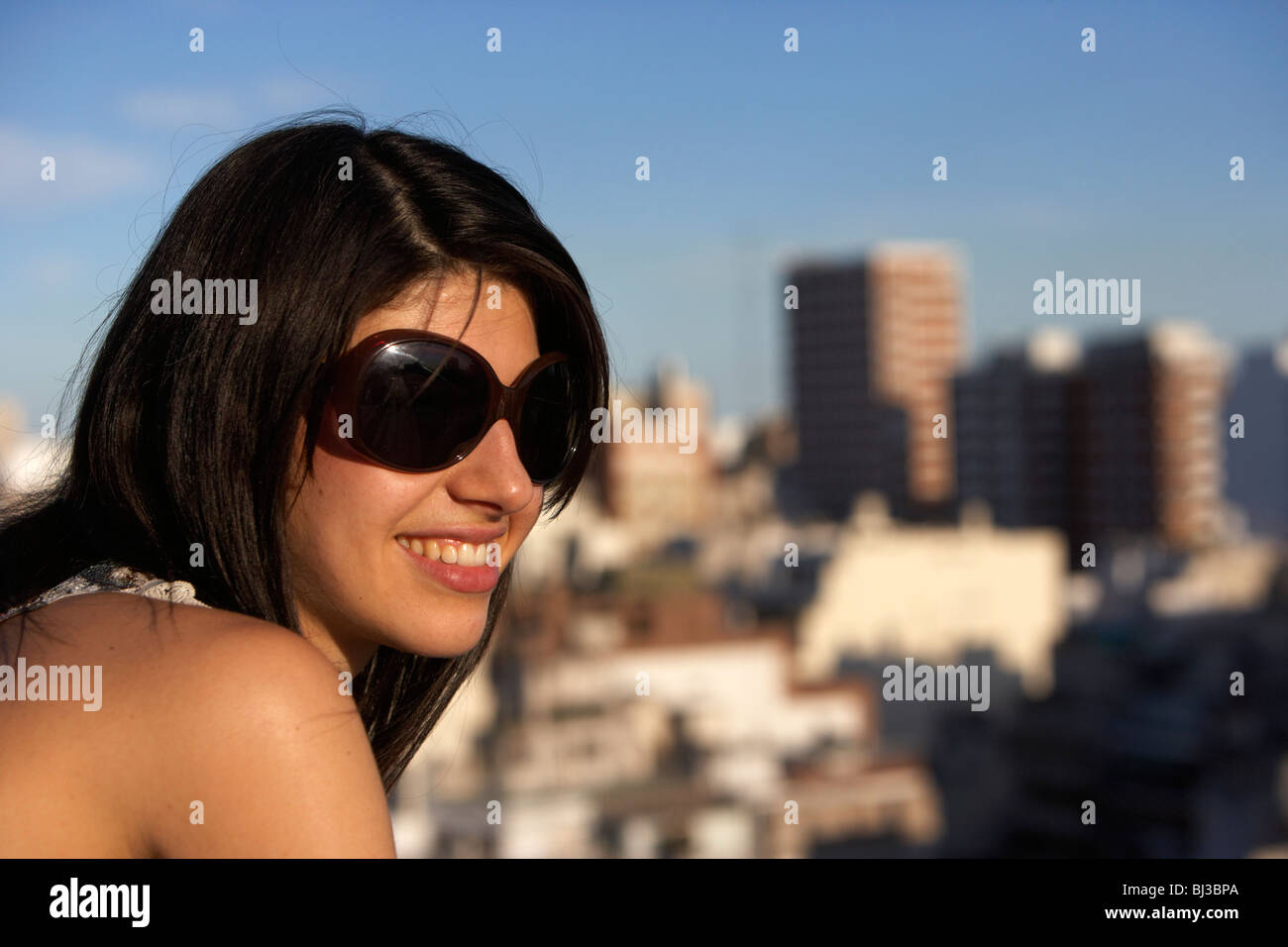 young hispanic latin woman with dark brown hair wearing sunglasses looking out on a hot summer day - Stock Image