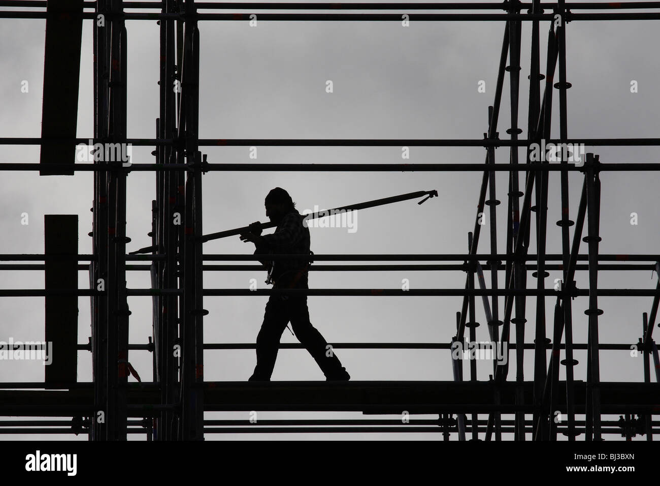 Silhouette of a workman on a scaffolding - Stock Image