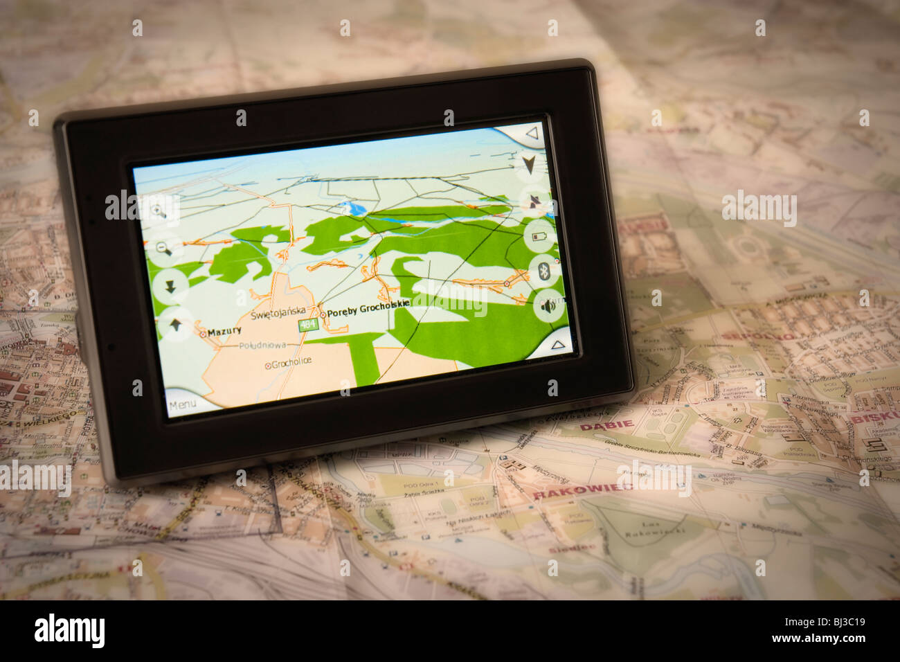 Portable GPS for a car sitting on a map - Stock Image