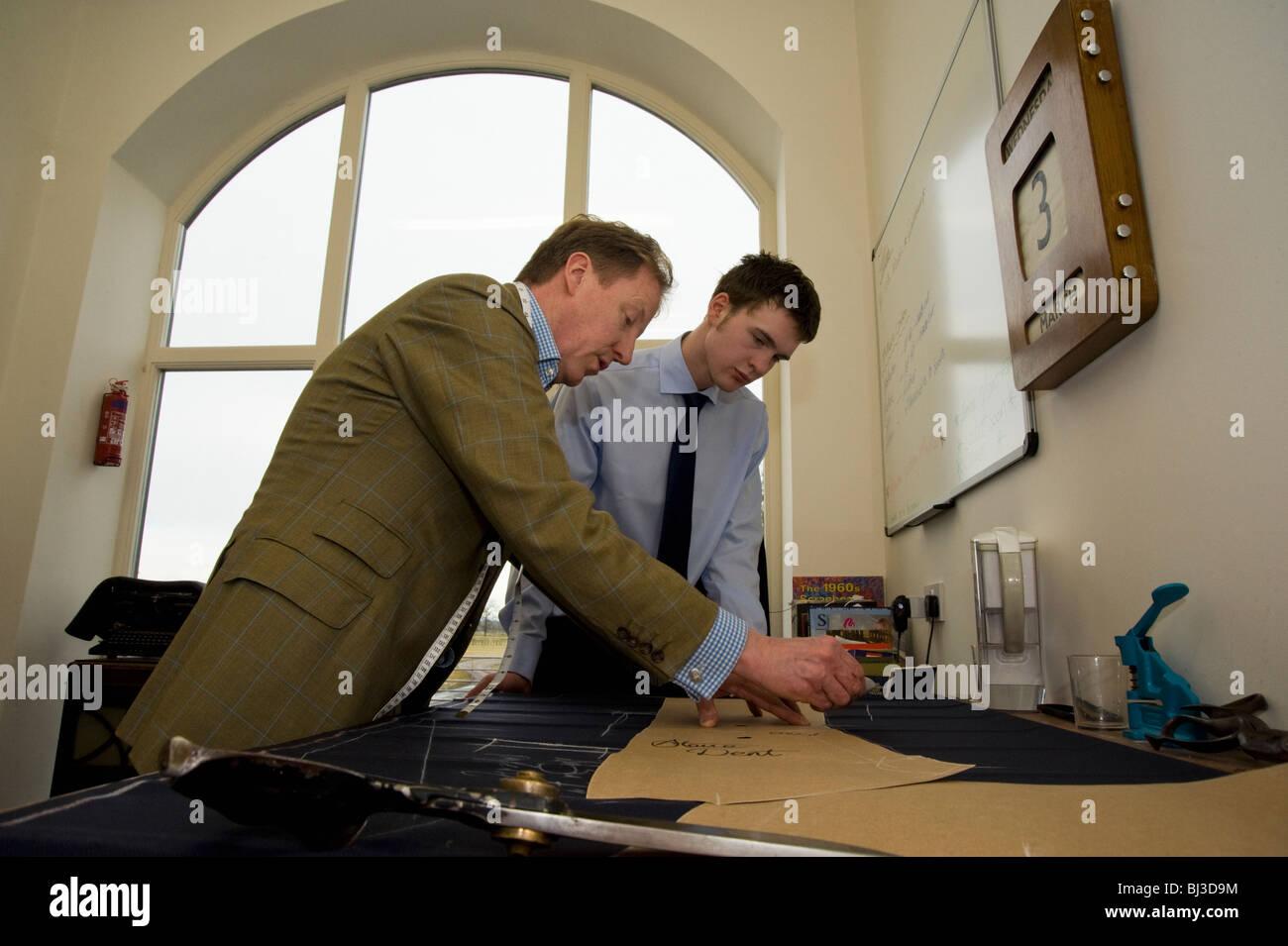 Master tailor Thomas Mahon instructing  his new apprentice the trade of tailoring at his Carlisle base Warwick Hall, - Stock Image