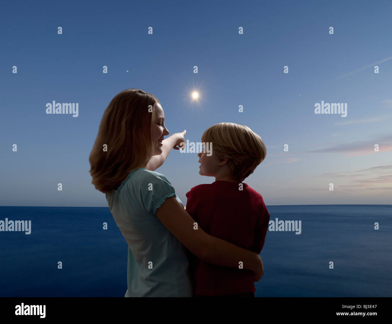 boy and girl watching the moon rising - Stock Image