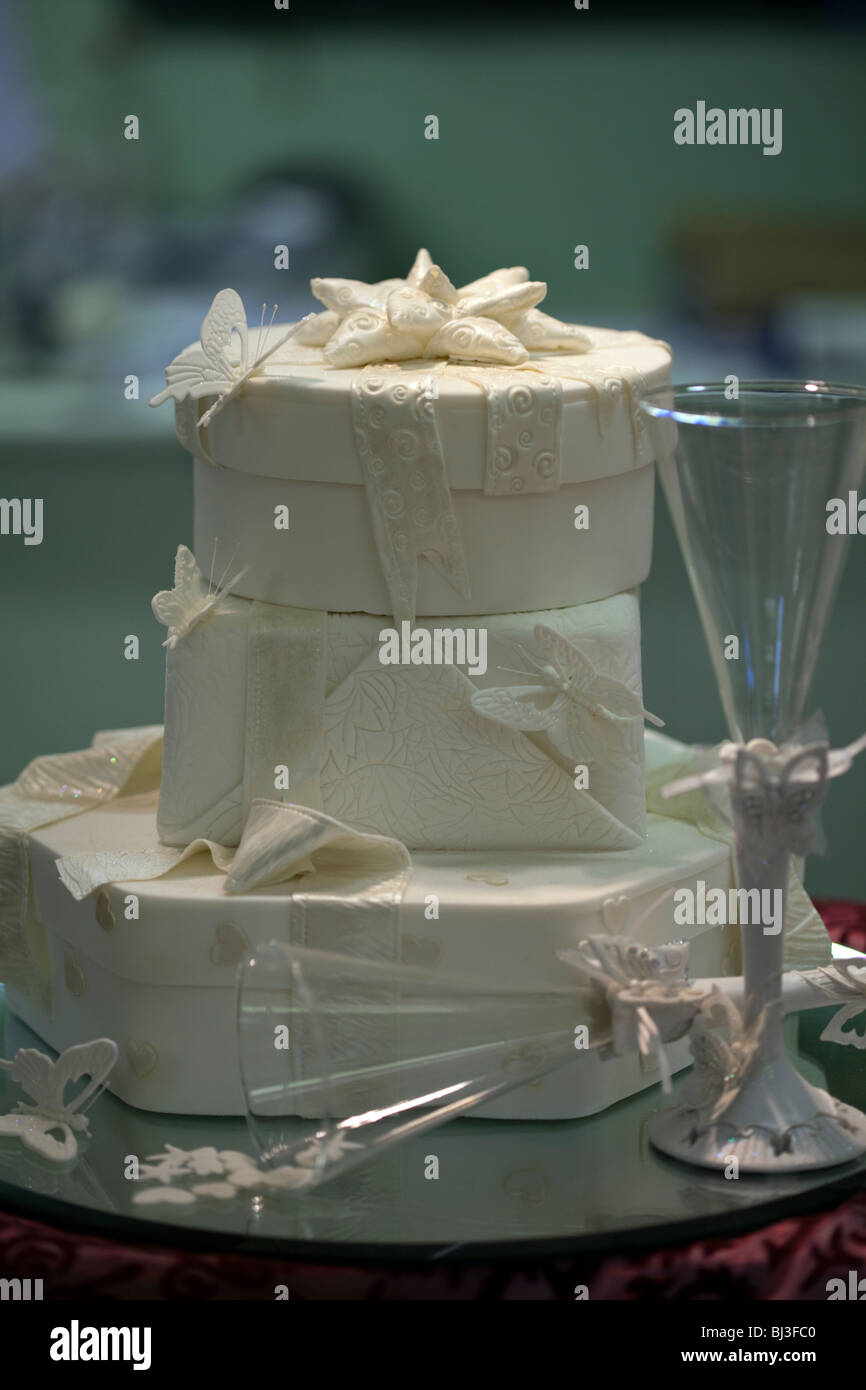 Wedding cake with bows and a  wine glass empty at the side - Stock Image