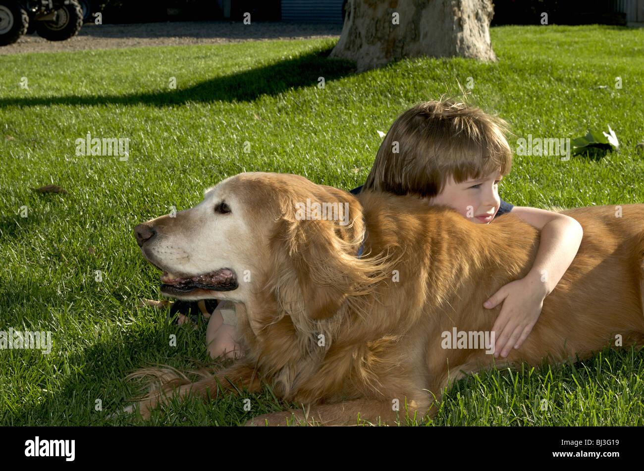 Boy rests on dog Stock Photo