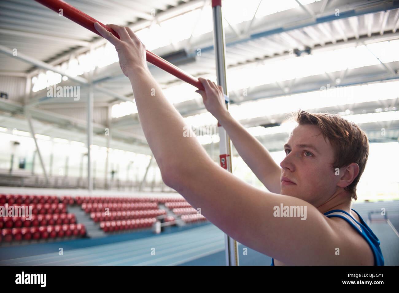 male athlete setting high jump bar - Stock Image